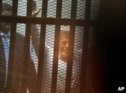 FILE - Egypt's ousted Islamist President Mohammed Morsi sits in a soundproof glass cage inside a temporary courtroom at Egypt's national police academy in Cairo, Egypt, Tuesday, April 21, 2015.