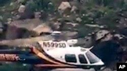 Dalam gambar 23 Juli 2017 yang diambil dari video yang dirilis oleh kantor Sheriff Pima County, seorang pendaki yang terdampar diselamatkan dari banjir bandang di dekat Tucson, Arizona.