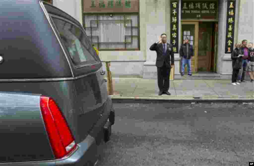 A man salutes as Pvt. Danny Chen's funeral procession passes on Thursday, Oct. 13, 2011 in New York. Chen was killed on Oct. 3 in a noncombat-related death in Kandahar province in Afghanistan. (AP Photo/Jin Lee)