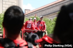 The players rode down Pennsylvania Avenue on buses during the parade.