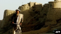 An Afghan man rides his bicycle through an old city area of Ghazni province, August 20, 2007. (Click to Expand)
