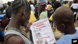 Liberian children read a leaflet with guidelines to protect the community from the Ebola virus, in Monrovia, Liberia. Monday, Oct. 13, 2014. Some nurses in Liberia defied calls for a strike on Monday and turned up for work at hospitals amid the worst Ebola outbreak in history. In view of the danger of their work, members of the National Health Workers Association are demanding higher monthly hazard pay. The association has more than 10,000 members, though the health ministry says only about 1,000 of those are employed at sites receiving Ebola patients. (AP Photo/Abbas Dulleh)