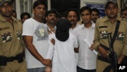Indian police officers escort Mumbai attacks suspect Syed Zabiuddin, face covered, out from a government hospital in New Delhi, India on June 29, 2012.