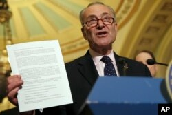 Senate Minority Leader Charles Schumer of N.Y., holds up a letter to Republicans about healthcare while speaking to the media, May 9, 2017, on Capitol Hill in Washington.