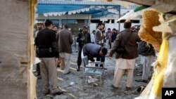 Pakistani security officials examine the site of a suicide attack in Mardan, Pakistan, Dec. 29, 2015.