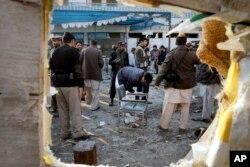 FILE - Pakistani security officials examine the site of a suicide attack in Mardan, Pakistan, Dec. 29, 2015.