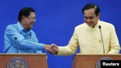 Cambodia's Prime Minister Hun Sen (L) and Thailand's Prime Minister Prayuth Chan-ocha shake hands during a news conference after an agreement signing ceremony at the Government House in Bangkok, Thailand, Dec.19, 2015.