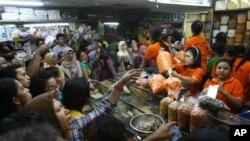 Para pembeli mengerumuni toko makanan yang menjual makanan kering untuk persiapan Ramadan dan Idul Firi di sebuah pasar di Jakarta (14/8/2012).