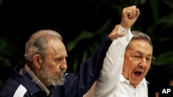 FILE - In this April 19, 2011 photo, Fidel Castro, left, raises his brother's hand, Cuba's President Raul Castro, center, as they sing the anthem of international socialism during the 6th Communist Party Congress in Havana, Cuba.