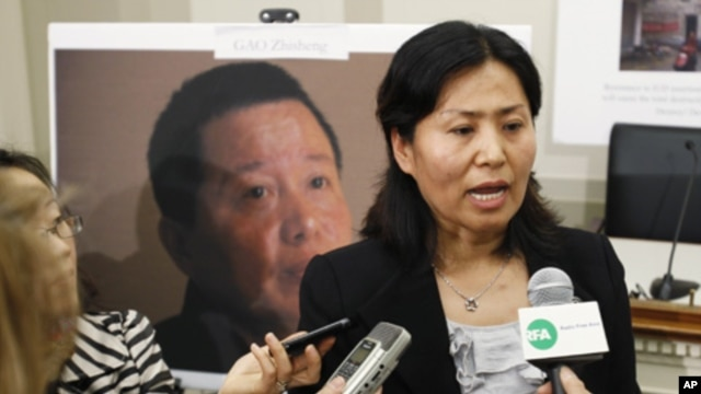 Geng He, the wife of Gao Zhisheng, a political prisoner and China's leading human rights lawyer, speaks in front of her husband's portrait during a news conference, Washington, 18 Jan 2011