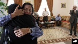 Dr. Fatima Haji, second left, hugs an unidentified woman after getting word of a judge's verdict Thursday, June 14, 2012, at a fellow doctor's home in Sehla, Bahrain.