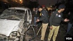 Polisi Pakistan memeriksa lokasi ledakan bom bunuh diri di Lahore, Selasa 25 Januari 2011.