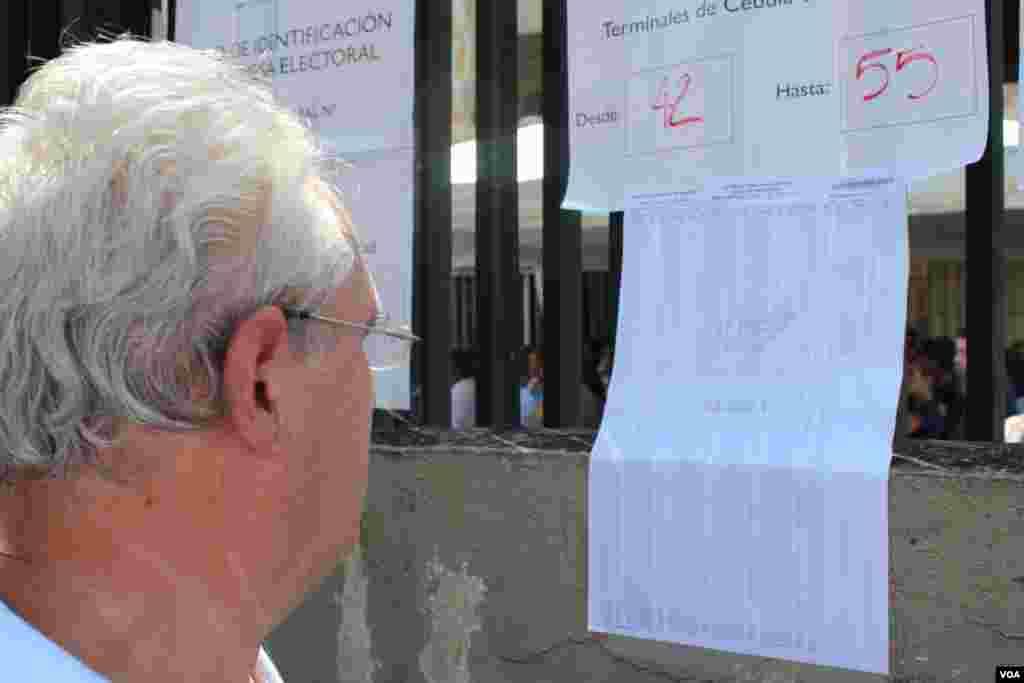 Un elector busca su nombre en la lista electoral para saber a qué mesa dirigirse en día de la elección en Caracas, Venezuela. [Foto: Iscar Blanco, VOA]