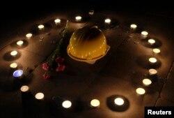 Mũ bảo hộ cho thợ mỏ và những bông cẩm chướng được đặt trên đất trong một buổi lễ thắp nến cầu nguyện cho những nạn nhân xấu số thiệt mạng trong vụ cháy mỏ than