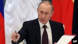 21일 러시아 모스크바에서 블라디미르 푸틴 대통령이 크림공화국 병합 문서에 서명하고 있다.