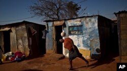 A South African woman, bounces the ball on her head while playing with a football next to their homes in a Soweto, township on the outskirts of Johannesburg, July 4, 2013.