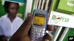 FILE - A man sending money through a mobile phone service called M-Pesa, in Nairobi.