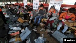 Employees sort packages at Shentong Express delivery company in Anhui province, following China's Singles' Day. It is celebrated annually on November 11 and has become the world's largest online shopping day (Reuters).