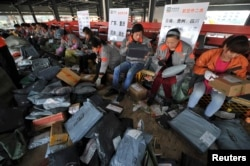 FILE - Employees sort packages at a hub of Shentong (STO) Express delivery company in Hefei, Anhui province.