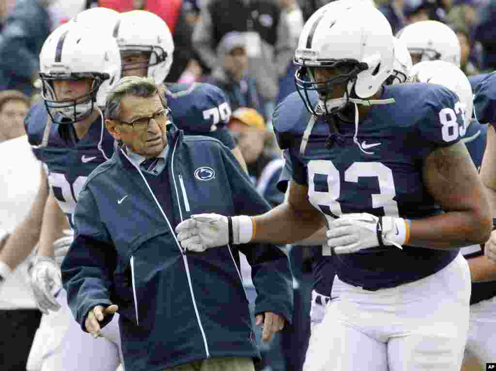 Penn State head coach Joe Paterno, left, gets out of the way of tight end Nate Cadogan (83) during warm-ups before an NCAA college football game against Purdue in State College, Pa., October 15, 2011 (AP)