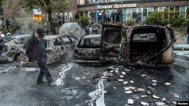 A bystander checks the debris around a row of burnt cars in the suburb of Rinkeby after youths rioted in several different suburbs around Stockholm, May 23, 2013.