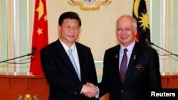 中国国家主席习近平(左)与马来西亚总理纳吉布10月4日在吉隆坡附近举行的记者会上