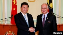 China's President Xi Jinping (L) and Malaysia's Prime Minister Najib Razak shake hands after their joint news conference at Najib's office in Putrajaya, near Kuala Lumpur Oct. 4, 2013.