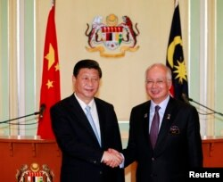 Presiden China Xi Jinping (kiri) dan PM Malaysia Najib Razak berjabat tangan seusai menggelar konferensi pers bersama di kantor PM Malaysia di Putrajaya, dekat Kuala Lumpur (4/10).