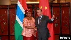 2016年3月17日北京: 中国外交部部长王毅(右)与冈比亚外长盖伊握手