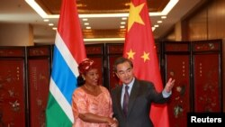 China's Foreign Minister Wang Yi (R) shakes hand with his Gambian counterpart Neneh Macdouall-Gaye during a meeting in Beijing, China, March 17, 2016.
