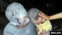 This citizen journalism image taken on April 25, 2013 and provided by Edlib News Network (which has been authenticated) shows a wounded Syrian man holding his injured son after an air raid on the town of Saraqeb in Idlib province.