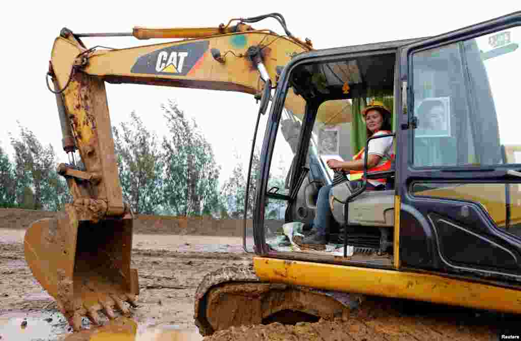 "Filipina Grace Ocol, 40, a backhoe operator, poses for a photograph in Tubay, Agusan del Sur, southern Philippines, Feb. 16, 2017. Ocol, a mother of three, said, ""There are a few female workers that can drive big trucks and backhoe. If men can do it, why can't women do it? I'm better than the men, they can only drive trucks here but I can drive both."""