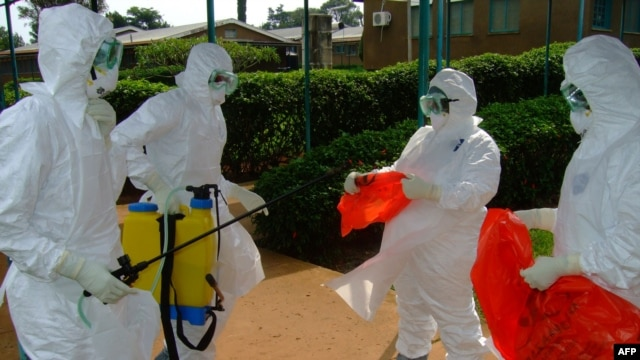 FILE - World Health Organization officials wear protective clothing as they prepare to enter Kagadi Hospital in Kibale District, about 200 kilometers from Kampala.