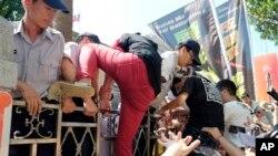Polisi mendorong demonstran yang berupaya memanjat pagar gedung badan legislatif Taiwan dalam aksi demo anti-perjanjian perdagangan Taiwan-China di Taipei, Taiwan (31/7).