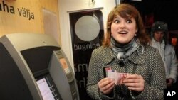 An Estonian woman holds one of the new Euro banknotes which she has just withdrawn from an ATM cash machine in Tallinn, Estonia, 01 Jan 2011.