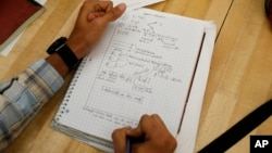 A student writes notes in the Advanced Placement (AP) Physics class at Woodrow Wilson High School in Washington, Friday, Feb. 7, 2014.