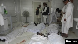 Afghan men stand over the bodies of a suicide bomb blast victims at a hospital in Khost province, June 20, 2012.