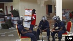 Cảnh sát Zambia ngồi trước cửa một trung tâm cộng đồng ở Lusaka, ngày 22/9/2011