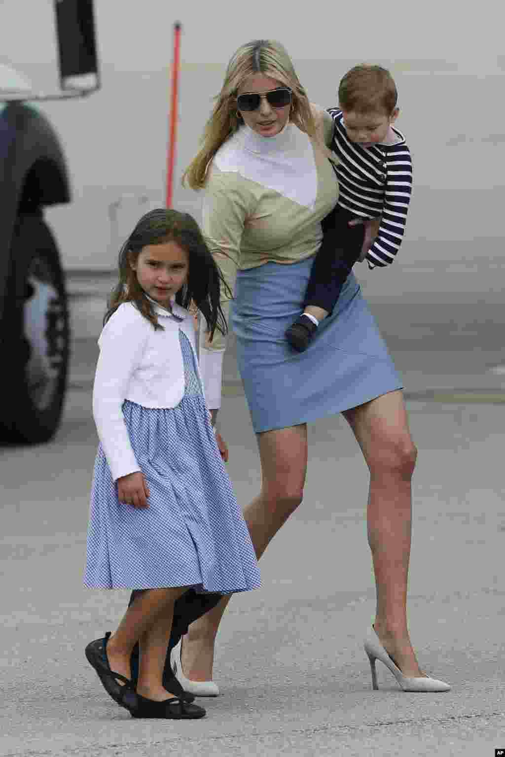 伊万卡·川普抱着小儿子,领着女儿和大儿子,离开总统专机后,走在西棕榈滩机场。她的女儿和大儿子当天晚上有给贵宾表演的任务 ——给贵宾习近平夫妇秀中文,唱《茉莉花》,背诵唐诗(2017年4月6日)