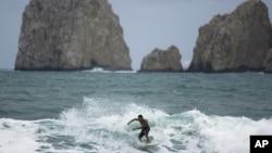 Un surfeador cruza las aguas de Cabo San Lucas en México. La zona fue sacudida este martes por dos fuertes temblores que provocó la evacuación momentánea de turistas.