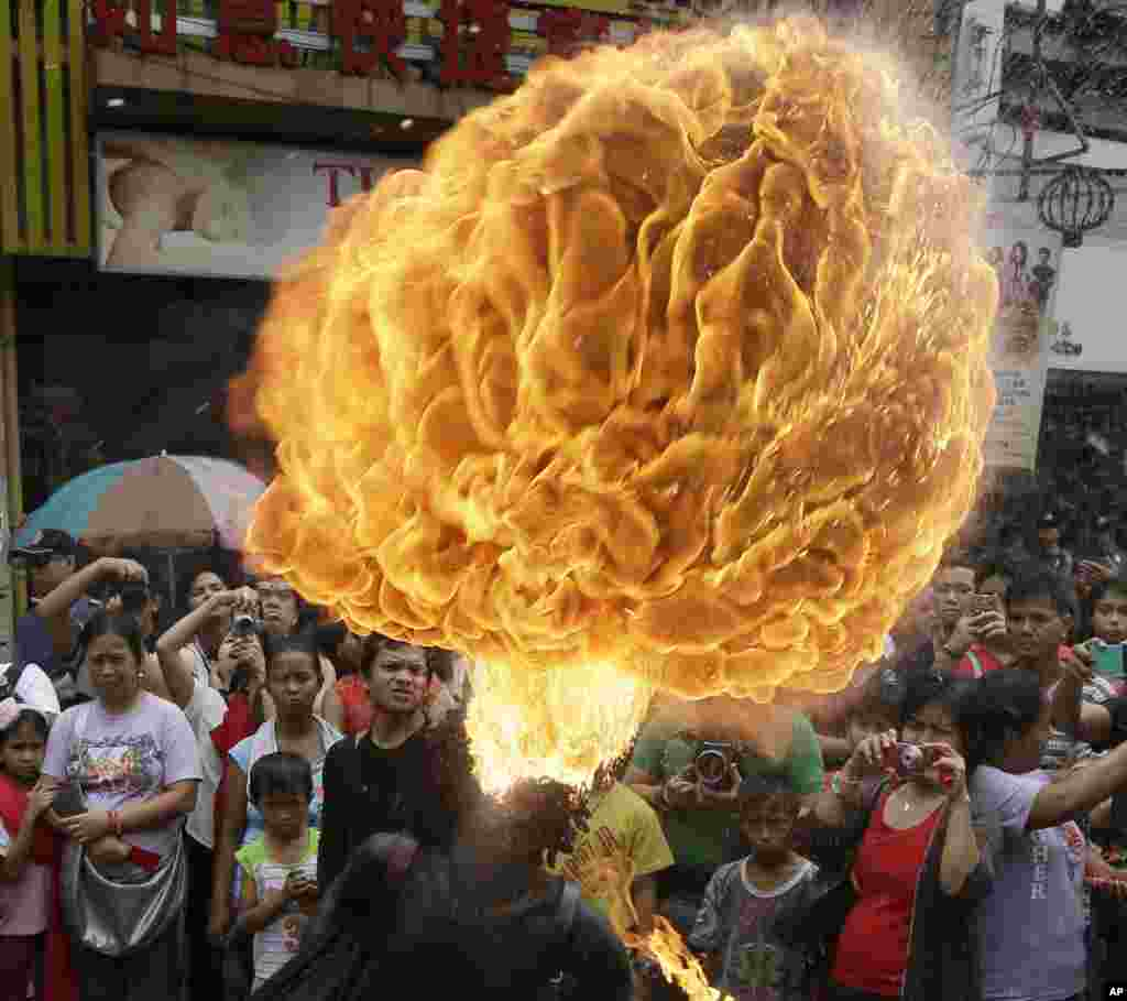 A fire-eater performs in Chinatown to celebrate the Chinese New Year, Manila, Philippines, Feb. 19, 2015.