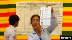 An election official shows a ballot paper as votes are counted at a polling station in Phnom Penh July 28, 2013.