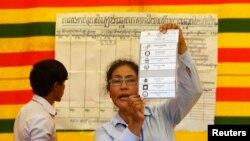 Giới chức bầu cử cầm một lá phiếu tại một địa điểm bầu cử tại thủ đô Phnom Penh, ngày 28/7/2013.