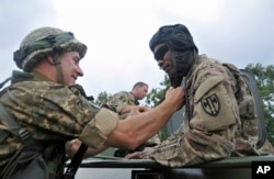 FILE - U.S. and Ukrainian servicemen talk during the opening ceremony for the Rapid Trident/Saber Guardian 2015 military exercises at the International Peacekeeping and Security Centre base outside Lviv, Ukraine, July 20, 2015.