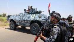 Des policiers fédéraux irakiens patrouillent à Abou Ghraib, dans la banlieue de Bagdad, en Irak, 28 juin 2014 .. AP, Bagdad