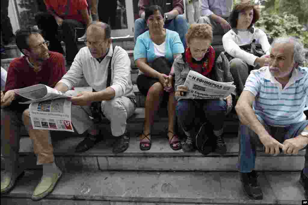 Protesters read newspapers outside Greek state television ERT headquarters during general strike in Athens, June 13, 2013.