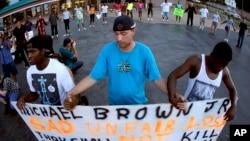 Cư dân đứng cầu nguyện sau khi diễu hành đến đồn cảnh sát để phản đối vụ bắn chết Michael Brown tại Ferguson, Missouri.