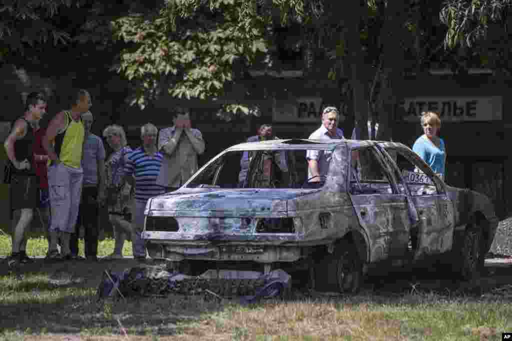 People look at a car following shelling from Ukrainian government forces, Slovyansk, Ukraine, May 28, 2014.