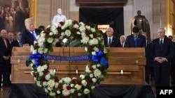 Le président américain Donald Trump, à gauche, met la main sur le cercueil de l'évangéliste Billy Graham à la rotonde du Capitol à Washington, le 28 février 2018