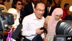 FILE - Malaysian opposition leader Anwar Ibrahim, center, arrives at court house in Putrajaya, Malaysia Tuesday, Feb. 10, 2015.